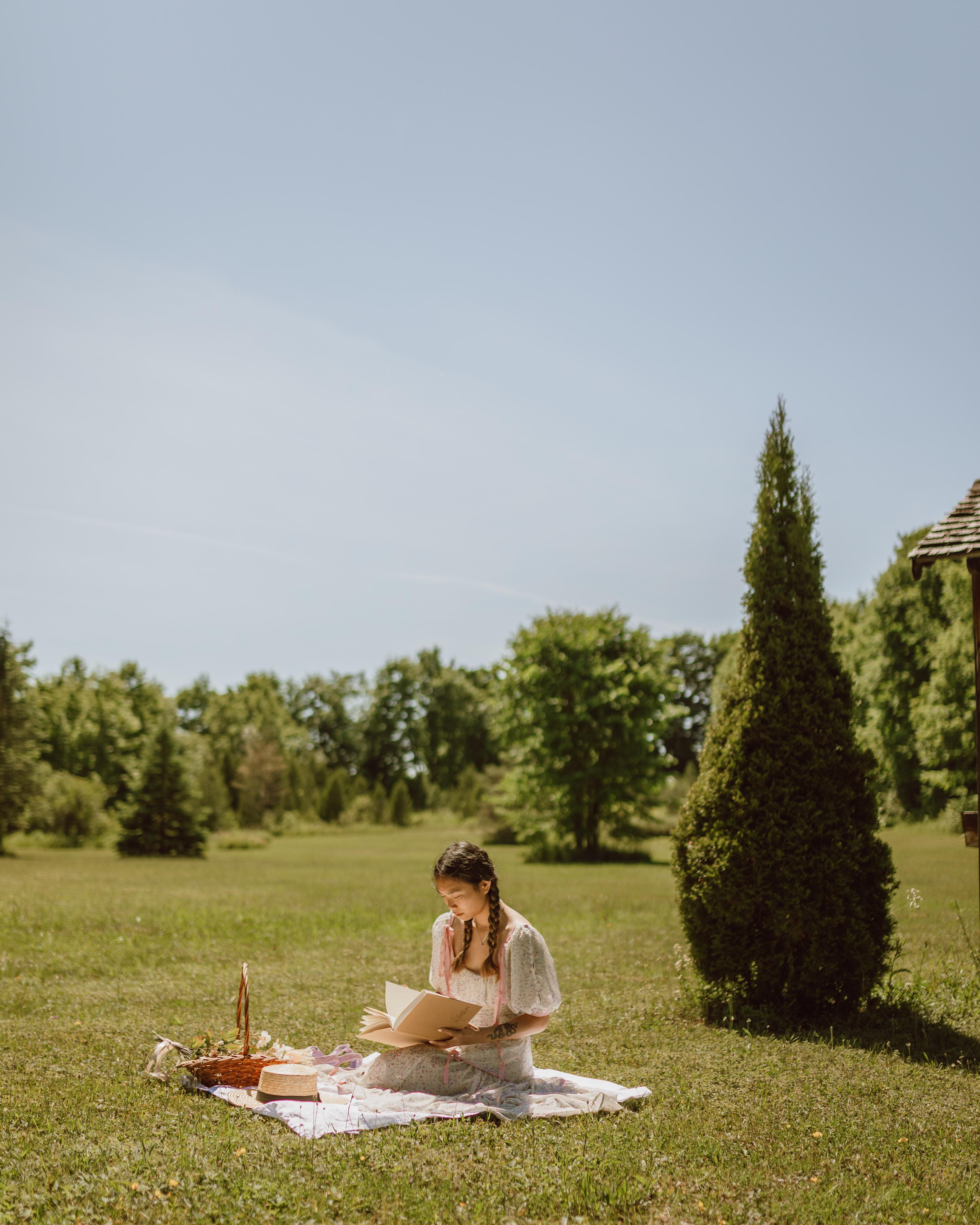 草地上看书的美女图片