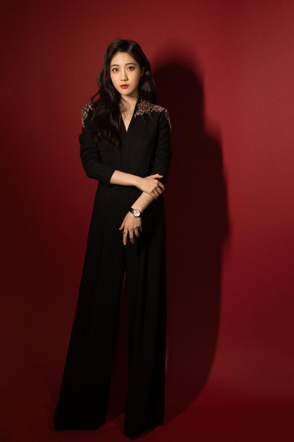 李艺彤红色背景下穿着黑色西装演出服写真图片