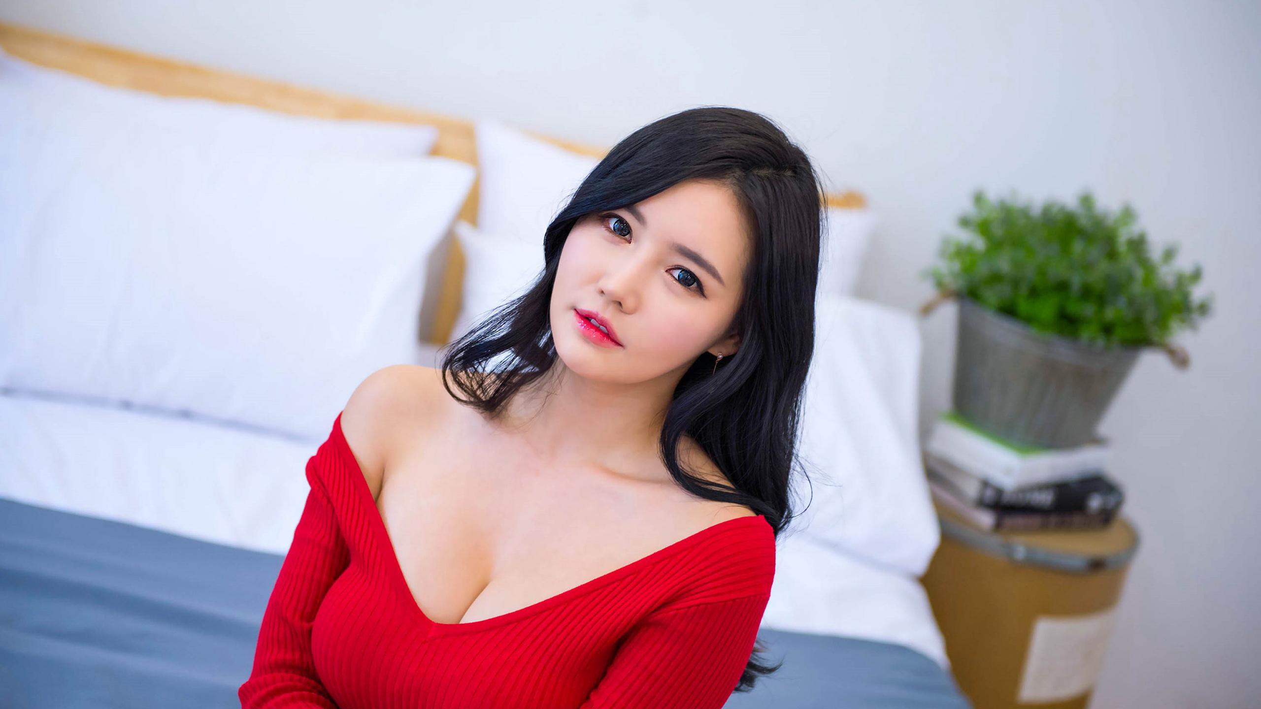 坐在床上穿红色低胸上衣的长发美女壁纸