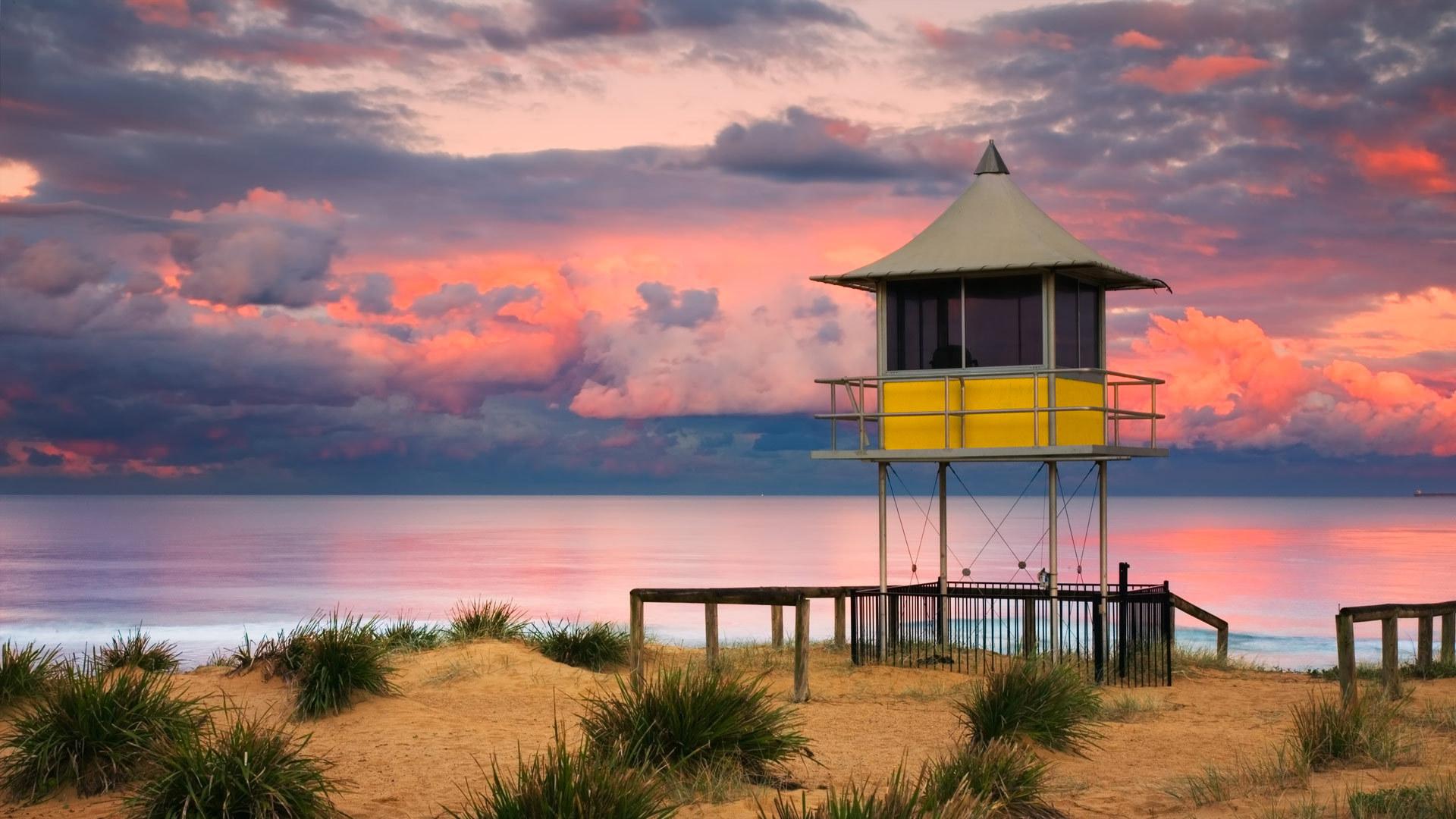 日落时分中央海岸入口海滩上的救生员小屋中央海岸