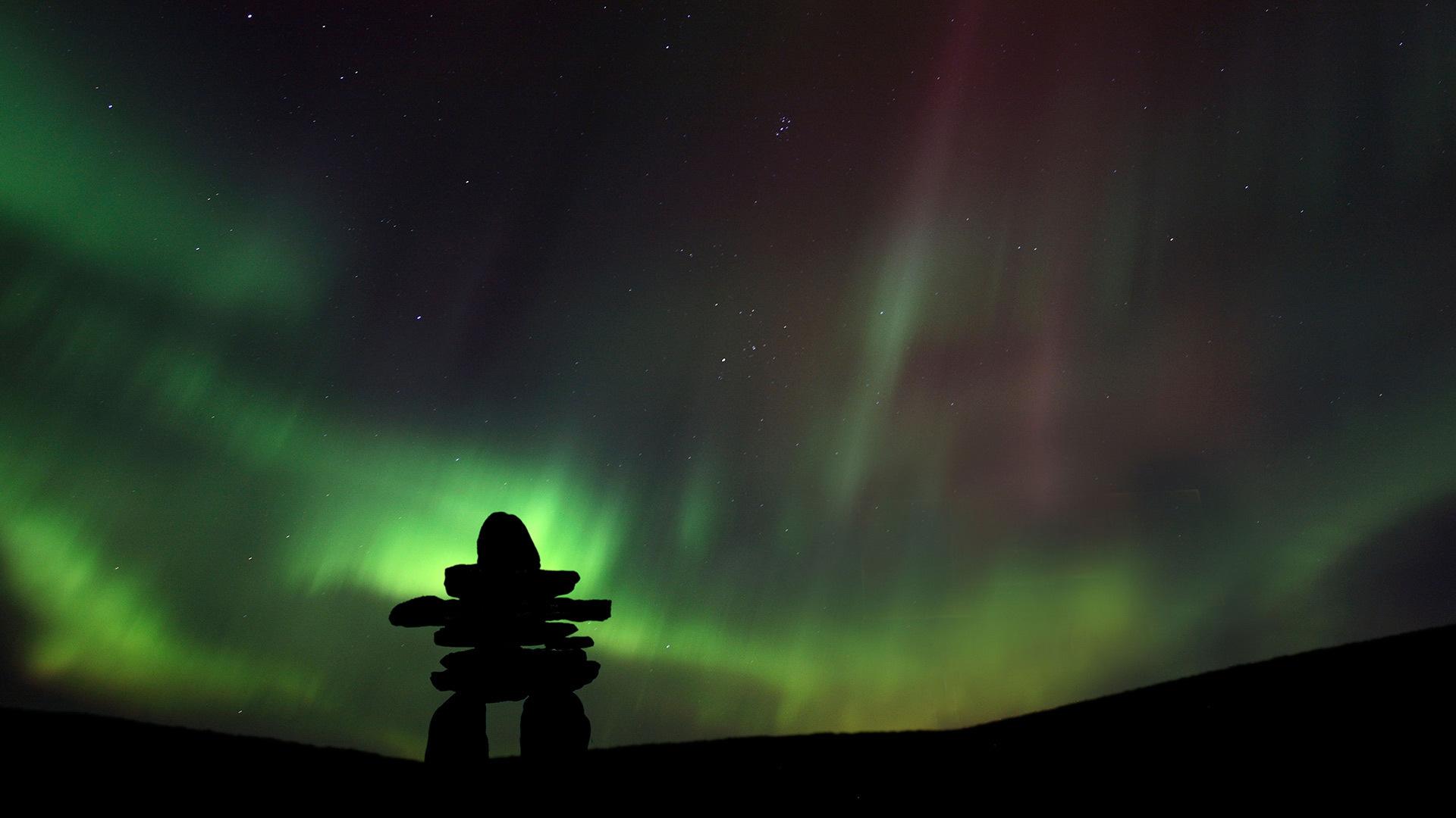 被北极光映衬出轮廓的因努伊特石堆北极光映