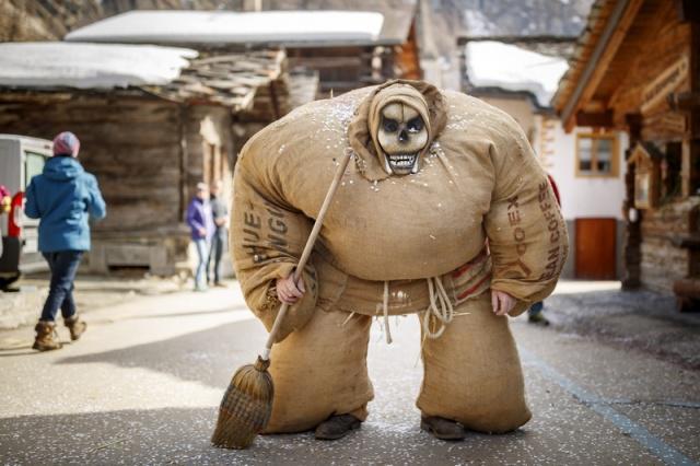 """瑞士埃沃莱纳,在冬季传统狂欢节上,民众身穿装满稻草的麻袋装扮成""""稻草人""""。 涨姿势 第4张"""
