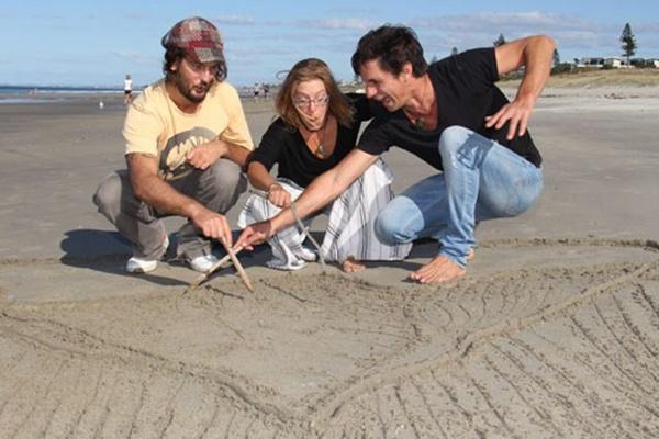 沙滩上三位艺术家正在创作